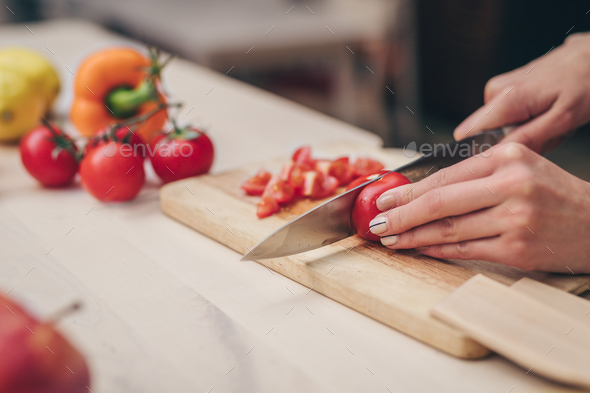Young woman cutting vegetables - Stock Photo - Images
