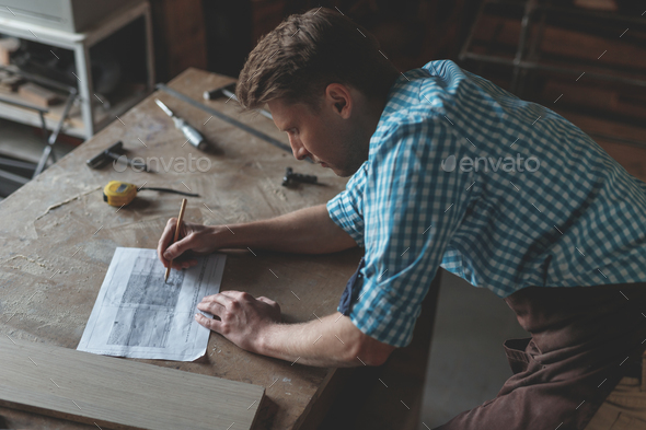 Young man at work in carpentry - Stock Photo - Images