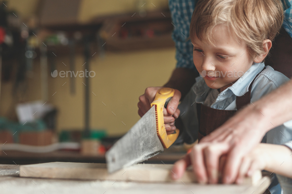 Little boy sawing a plank - Stock Photo - Images