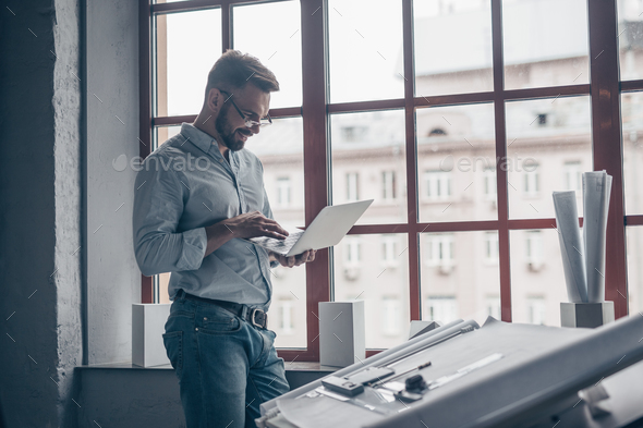 Mature man with laptop by the window - Stock Photo - Images