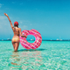Young woman in bikini with pink donut swim ring in the sea - PhotoDune Item for Sale