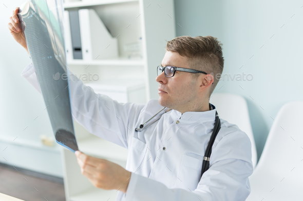 Handsome bearded doctor checking X-ray image - Stock Photo - Images