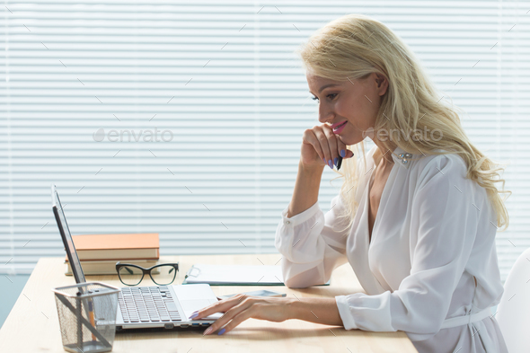 Young woman working in office wuth laptop and writing notes - Stock Photo - Images