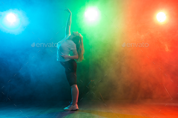 People and dancing concept- European young woman dancing jazz funk over  colored background