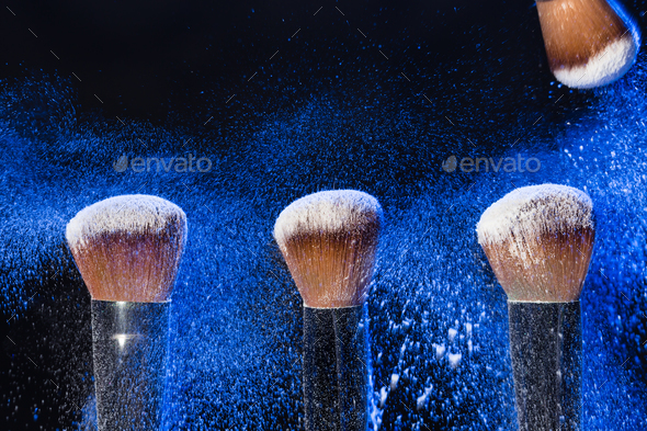 Make up, beauty and mineral powder concept - brush with blue powder on black background - Stock Photo - Images