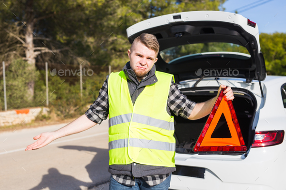 At the man of a trouble with a car he gets a red triangular emergency sign - Stock Photo - Images