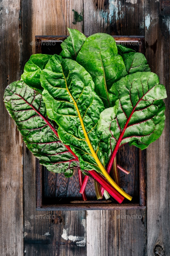 Fresh raw swiss rainbow chard leaves on wooden background. - Stock Photo - Images
