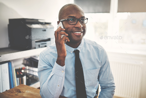 Smiling African businessman talking on a cellphone in an office - Stock Photo - Images