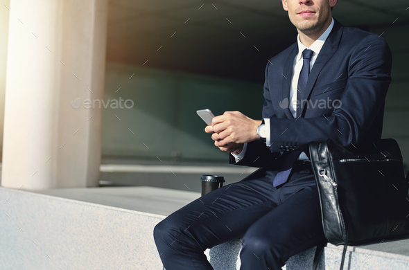 Man wearing suit holding a gray cellphone - Stock Photo - Images