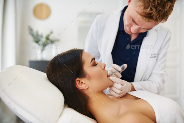 Young male doctor doing botox injections on a woman's lips - Stock Photo - Images