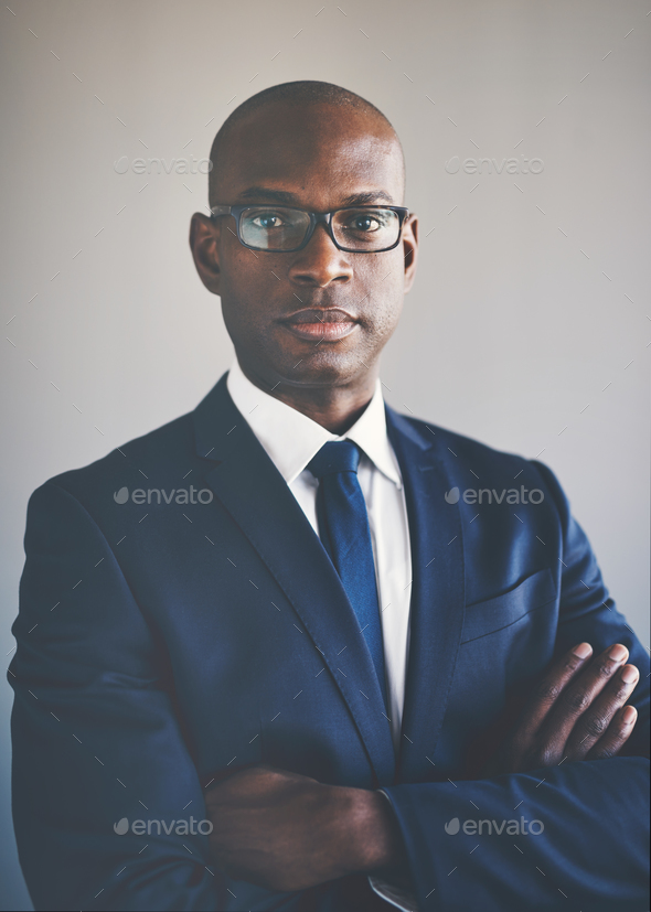 African executive in a suit standing wth his arms crossed - Stock Photo - Images