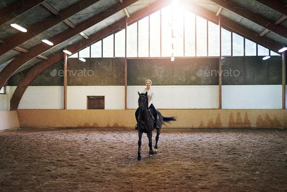 Female riding dark horse in indoor paddock - Stock Photo - Images
