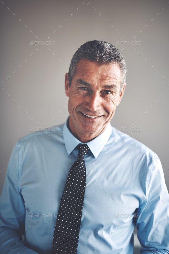 Smiling mature corporate executive wearing a shirt and tie - Stock Photo - Images