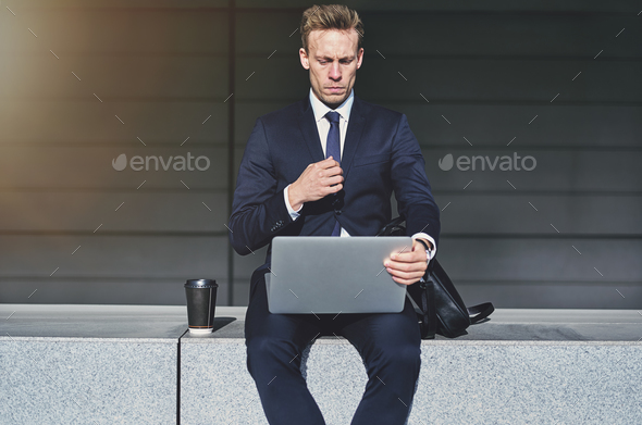 Serious handsome businessman turning on his laptop - Stock Photo - Images