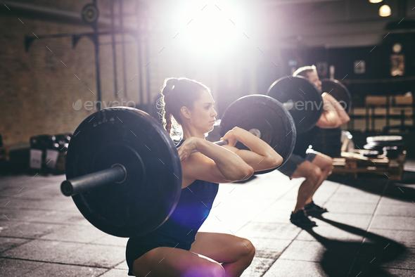 Man and woman lifting barbells at gym - Stock Photo - Images