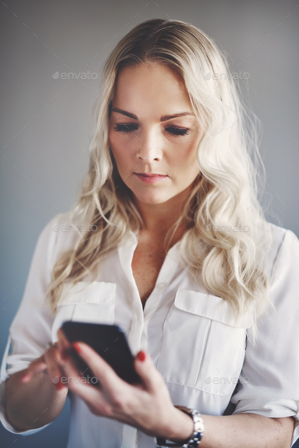 Young businesswoman sending text messages on a cellphone - Stock Photo - Images