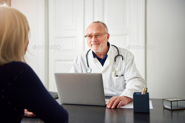 Therapist listening to patient at laptop in hospital - Stock Photo - Images