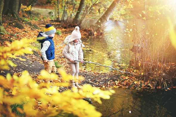 Two kids with branch near the pond - Stock Photo - Images