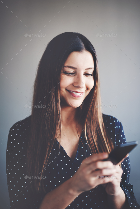 Smiling young businesswoman standing alone reading messages on a cellphone - Stock Photo - Images