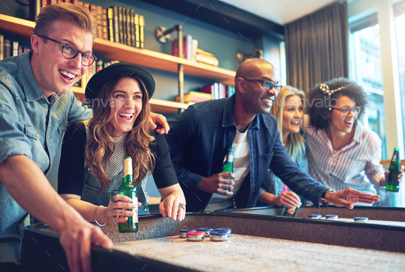 Mixed race friends playing game at bar - Stock Photo - Images