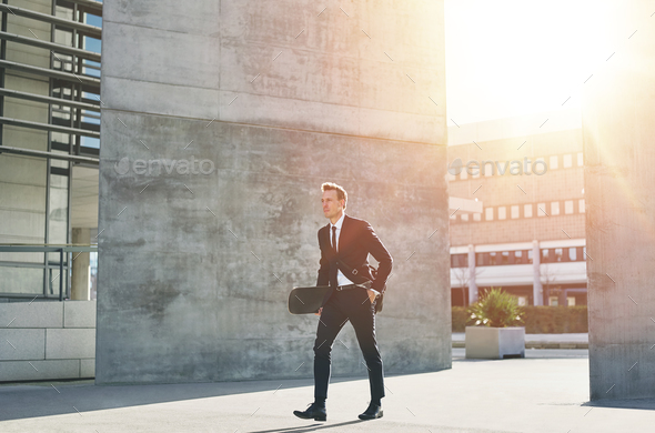 A businessman carries a skateboard in downtown - Stock Photo - Images