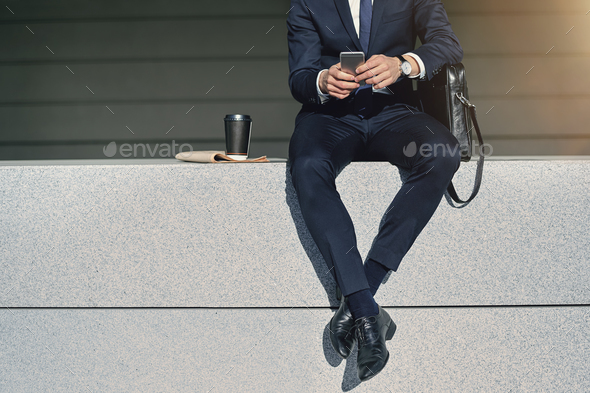 Legs of businessman searching information in smartphone - Stock Photo - Images