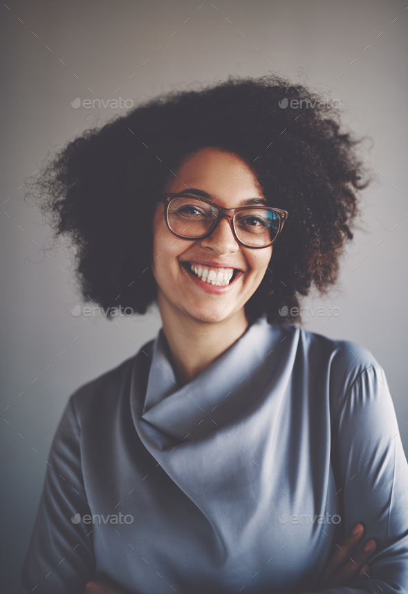 Smiling young African businesswoman standing with her arms crossed - Stock Photo - Images