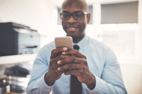 Smiling African businessman using a cellphone in an office - Stock Photo - Images
