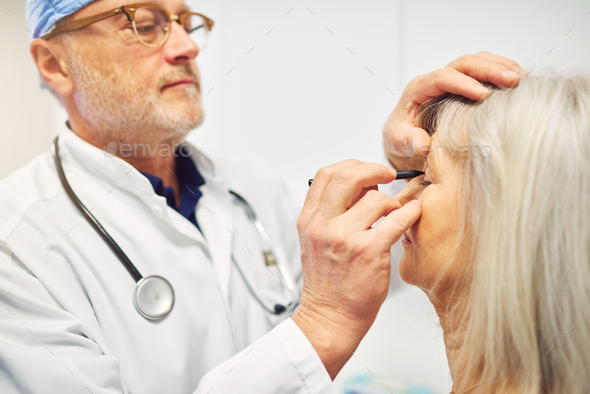Doctor drawing with marker on adult patient face - Stock Photo - Images