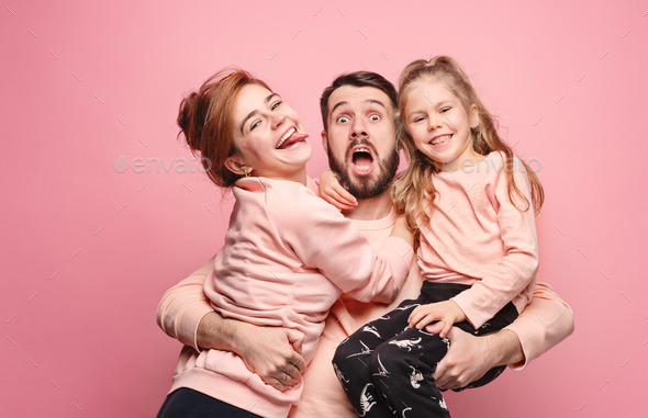 Happy young family with one little daughter posing together - Stock Photo - Images