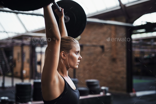 Fit young woman weightlifting alone in a gym - Stock Photo - Images