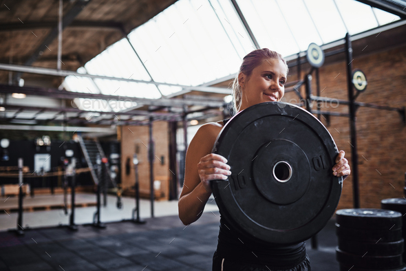 Smiling young woman selecting weights for a gym workout - Stock Photo - Images