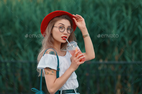 A Young stylish woman having a refreshing drink while walking - Stock Photo - Images