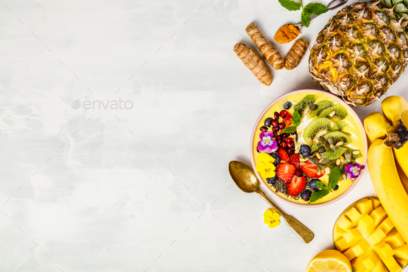 Mango banana pineapple turmeric smoothie bowl - Stock Photo - Images