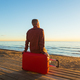 Man sitting on red suitcase near the sea and watching to the sunset - PhotoDune Item for Sale