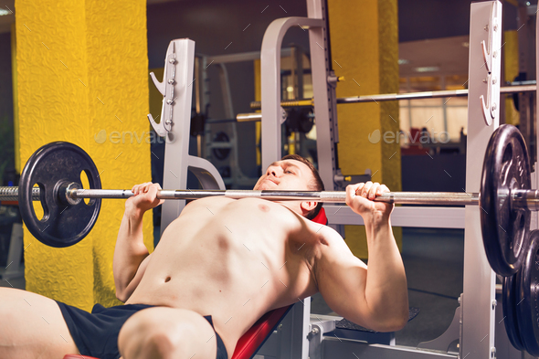 Man doing heavy exercise pumping up muscles on bench press - Stock Photo - Images
