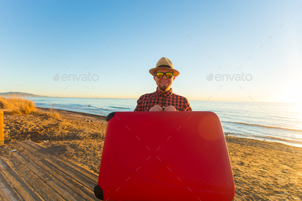 Man in glasses and hat carring his red suitcase near the sea - Stock Photo - Images