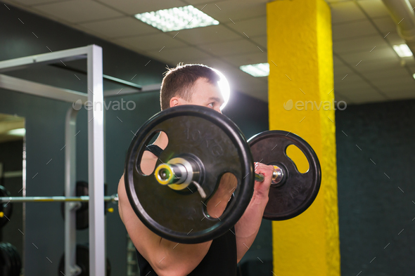 Muscular young man lifting weights in gym - Stock Photo - Images