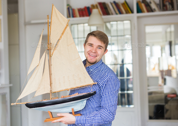 Hobby, collecting, ship and people concept - handsome man holding layout of a sailboat - Stock Photo - Images