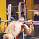 Man doing heavy exercise pumping up muscles on bench press - PhotoDune Item for Sale