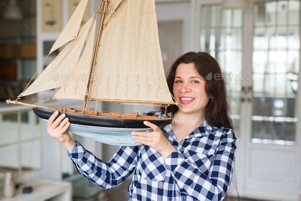 Hobby, collecting, ship and people concept - young woman holding layout of a sailboat - Stock Photo - Images