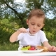 A Little Boy Sitting at a Table in the Background of a Green Forest and Eating Meat Cooked - VideoHive Item for Sale