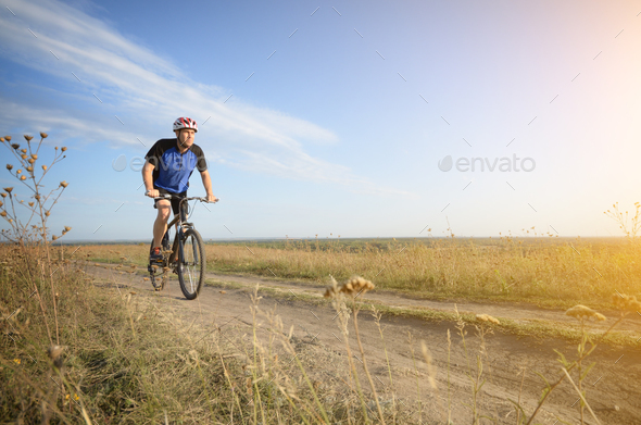 Male cyclist driving by rural dirt road outdoors - Stock Photo - Images