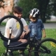Curious Child Wearing Helmet Is Spinning Bicycle Wheel and Pedals While His Father Is Talking To Him - VideoHive Item for Sale