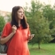 Beautiful Pregnant Girl Expecting Mother Is Walking in City Park and Using Smartphone, Young Woman - VideoHive Item for Sale
