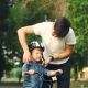 Caring Father Is Putting Safety Helmet on His Little Son's Head - VideoHive Item for Sale