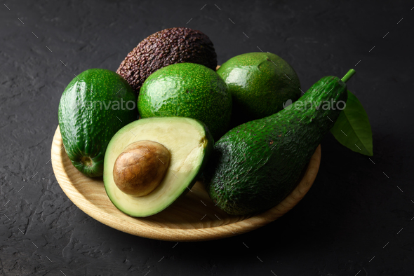 Fresh avocado fruit on a wooden plate - Stock Photo - Images