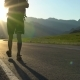 A Young Tourist with a Backpack Goes on the Road in a Mountainous Area. - VideoHive Item for Sale