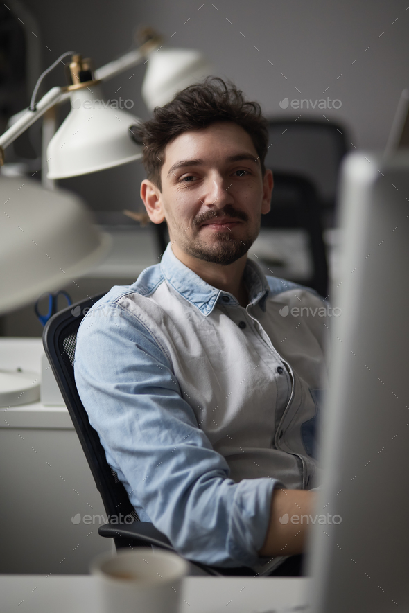 Young intelligent man working at modern loft studio-office with - Stock Photo - Images