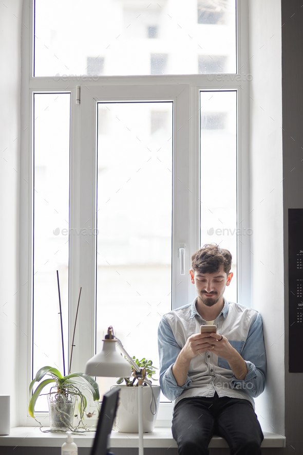 Young stylish man sitting on the window with phone in hands - Stock Photo - Images